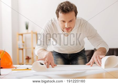 Give me enough time. Delighted man keeping smile on his face opening big paper roll while looking straight