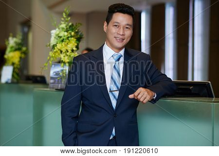 Confident Asian hotel owner with hand in pocket leaning on front desk and looking at camera with wide smile, waist-up portrait