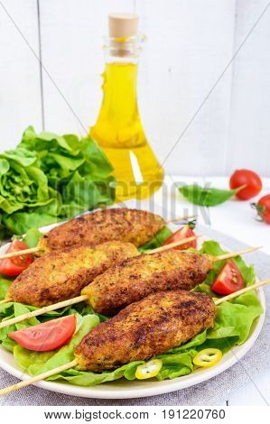 Lula-kebab is a meat dish traditional for the Caucasus in Central Asia and Turkey. Minced meat strung on a skewer and fried. Serve on a plate with lettuce leaves and fresh tomatoes. Vertical view