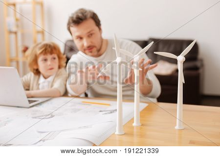 The way it works. Competent man sitting near his son talking to him while actively gesticulating