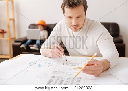 Working at the moment. Handsome man sitting at his workplace and looking forward while going to draw model of turbine
