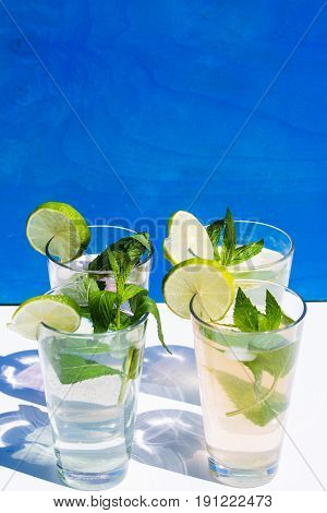 Lemonade against blue background with mint and lime
