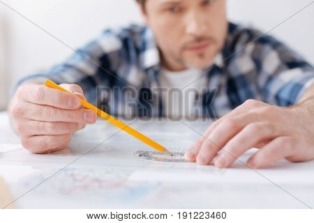 Serious task. Confident male person putting hands on the table while drawing sketch of the turbine