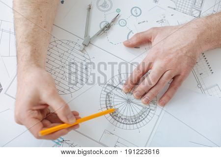 Do not make mistake. Accurate professional keeping pencil in right hand and using protractor for measuring grades while inventing windmills