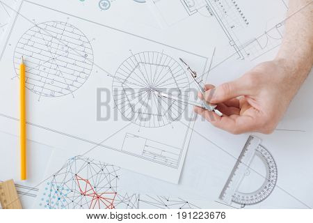 Use pair of compasses. Top view photo of special sketch where engineer counting the difference between turbines