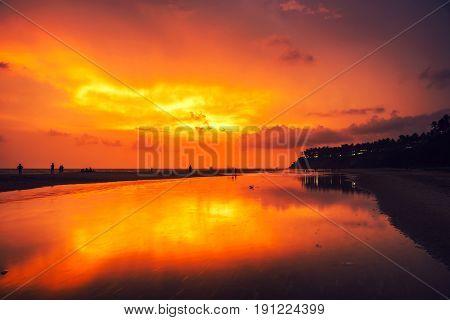 Kerala India. Varkala beach at night multiple colors colorful sunset sky and motion blurred Laccadive Sea at Papanasam beach in Kerala India
