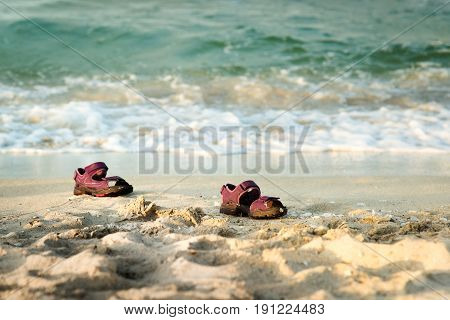 Pair of child sandals forgotten at the beach