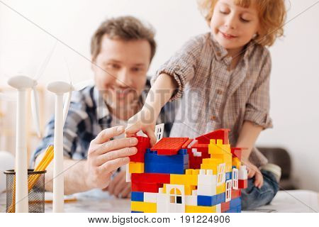 Building sphere. Enigmatical blonde kid with curly hair standing near his father and keeping smile on his face while making toy house