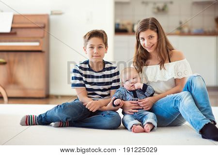 Portrait of young pretty teenage girl with her baby brother and 9 years old brother