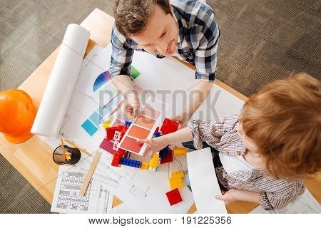 Want such bed. Handsome bearded man holding palette with red colors in right hand and detail from the meccano in left one while looking at his favorite child