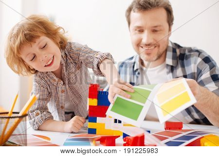 Stop working. Handsome boy leaning right elbow on the table while standing near his father and going to play with erector set