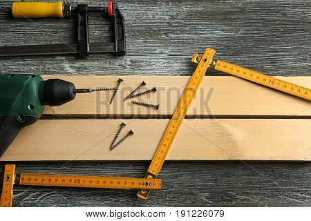 Set of tools and wooden boards on table in carpenter's workshop