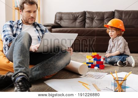 Wearing helmet. Handsome man-child sitting on the floor near his meccano and looking at his dad that working with laptop at the moment