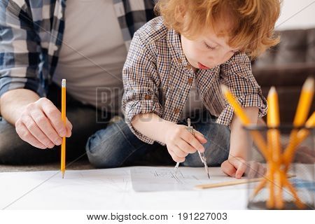 Be careful. Infatuated kid bowing head while doing circle on big sheet of paper and sitting near his father