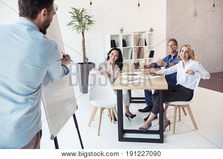 Businessman Writing On Whiteboard While His Colleagues Sitting At Table At Meeting