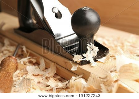 Bench plane, wooden boards and saw dust on table in carpenter's workshop, closeup
