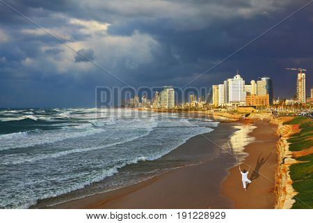 Storm cloud hanging over the sea, the woman in white performs yoga on one leg. Promenade and beach in Tel Aviv