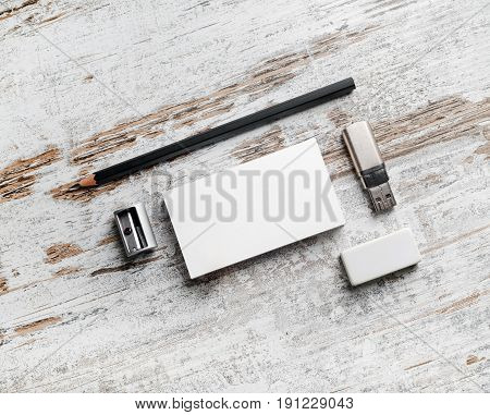 Photo of blank stationery set. Branding mockup. Bank white business cards pencil flash drive and sharpener on vintage wood table background.