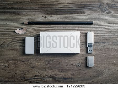 Business cards pencil eraser flash drive and sharpener on wood table background. Blank stationery set. Mock up for branding identity with plenty of copy space. Top view.