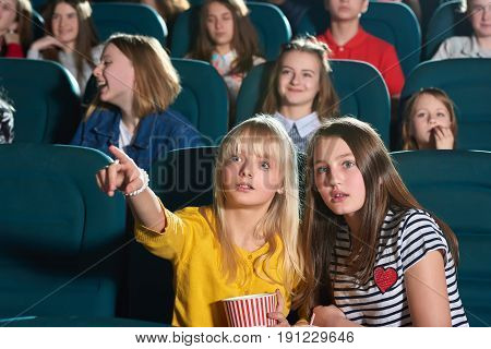 Young pretty girl looking surprised pointing at the movie screen at the cinema showing her friend something copyspace entertainment expressive emotions shock surprised hobby premiere tickets concept.