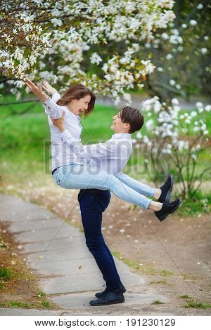 Woman sincerely glad to meet with her beloved under blossoming tree of magnolia. A man is holding a happy husband in his arms.
