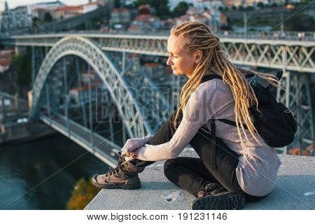 Young pretty woman with blond dreadlocks sitting on the view point in front of the Douro river and Dom luis I bridge in Porto, Portugal.