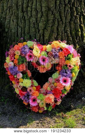 Heartshaped pastel sympathy flowers or funeral flowers near a tree