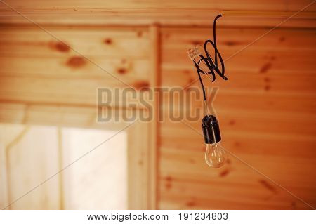 vintage lamp bulb hanging inside of a new wooden house