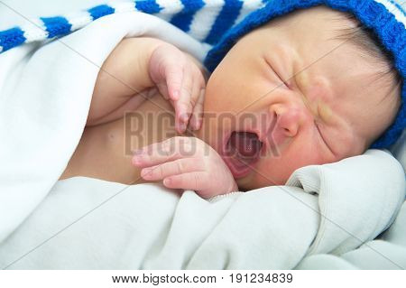 funny baby face in hatnewborn with jaundice on white blanket infant healthcare concept