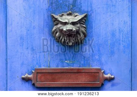 Metal doorknocker and red letter box on a blue wooden door