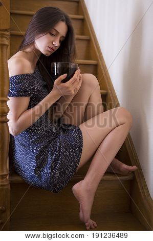 the beautiful woman at home on stairs with cup of tea