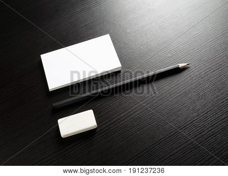 Photo of blank stationery set on black wooden table background. Bank business card pencil and eraser. Template for ID. Responsive design mockup. Top view.