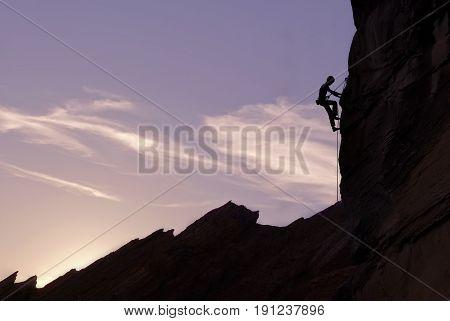 Man rock climber silhouette over bright sun background