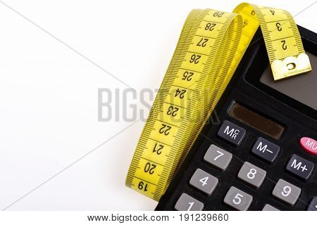 Calculate your diet. Plastic calculator with folded yellow sewing centimeter isolated on white background. Concept of dieting and measurement
