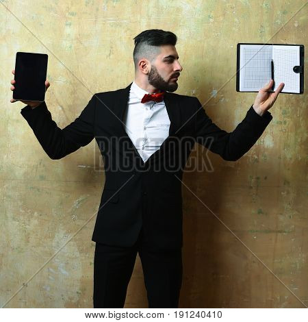 Business Executive With Neat Beard Holding Open Notepad And Tablet