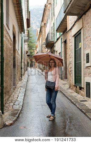 girl with an umbrella on a narrow European street