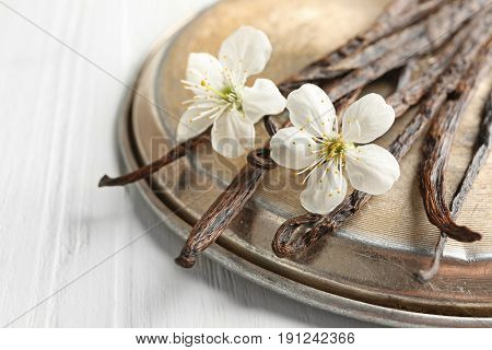 Dried vanilla sticks, flowers and metal plate on light wooden background, closeup
