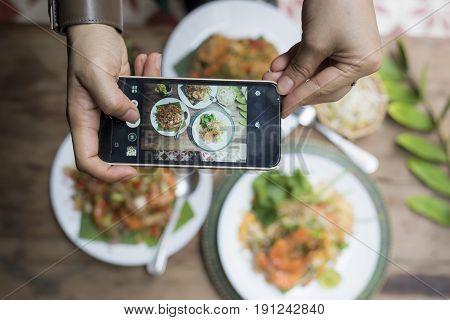 Food series: Variety of Thai food, Pad-Thai, deep fried prawns being photographed by smartphone