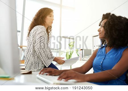 Profile view of attractive young employee sitting in front of modern computer and analyzing results of accomplished work with her female colleague