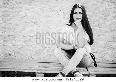 Portrait Of A Beautiful Girl Sitting On Wooden Boards Against Veneer Wall. Black And White Photo.