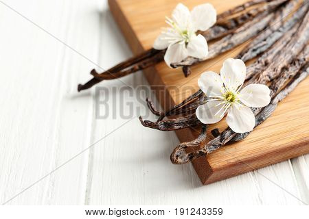 Dried vanilla sticks, flowers and board on light wooden background, closeup