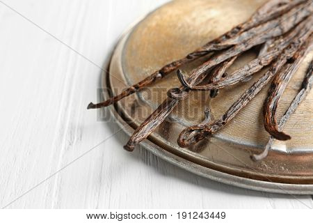 Dried vanilla sticks and metal plate on light wooden background, closeup