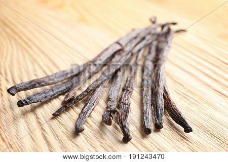 Dried vanilla sticks on wooden background, closeup