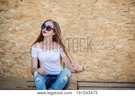 Portrait Of A Beautiful Girl Sitting On Wooden Boards Against Veneer Wall.