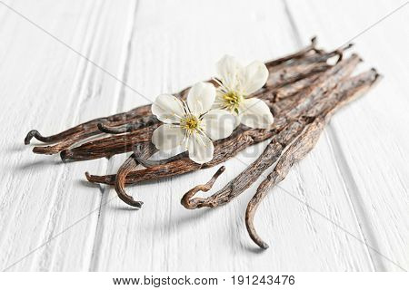 Dried vanilla sticks and flowers on light wooden background, closeup
