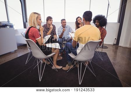 Serious business people disscussing plans while sitting in creative office