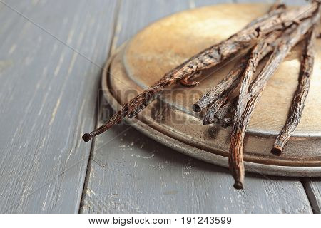 Dried vanilla sticks and metal plate on wooden background, closeup