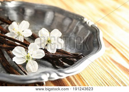 Metal plate with dried vanilla sticks and flowers on wooden table, closeup