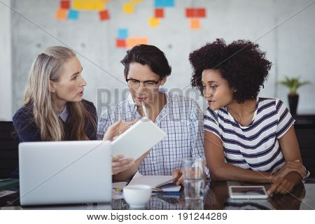 Confident business people using digital tablet while making strategies in creative office