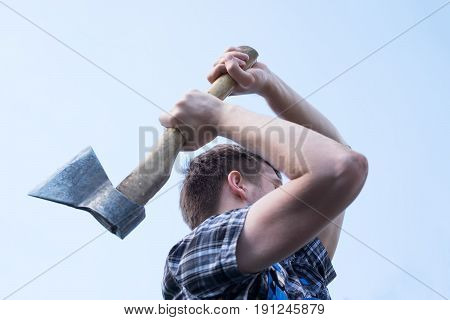 Portrait of confident man choping firewood with axe on shoulder